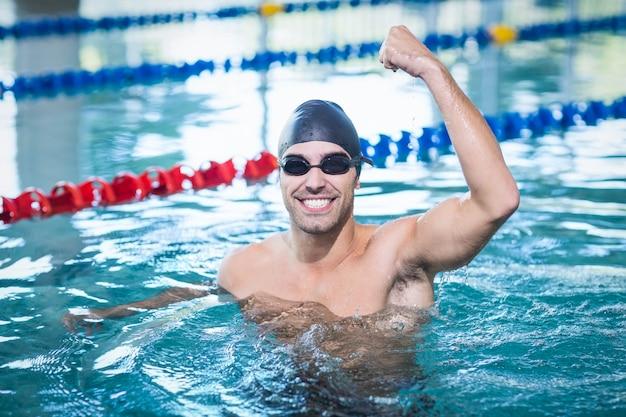 Homem bonito, triunfando com o braço levantado na piscina