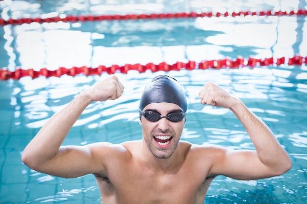 Homem bonito, triunfando na água na piscina