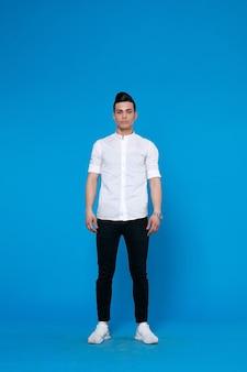 Homem bonito usa jaqueta de couro preta. foto de corpo inteiro de um jovem casual em pé com a jaqueta no ombro e a mão no bolso enquanto olha para a câmera. no fundo azul