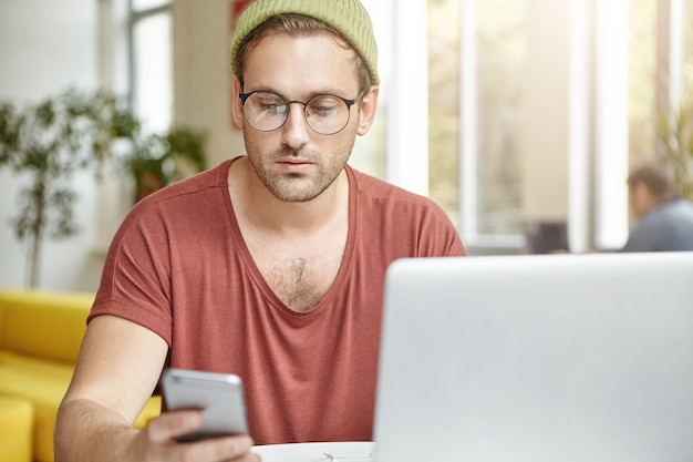 Homem bonito usa óculos redondos da moda, chapéu e camiseta, mensagem de texto no smartphone