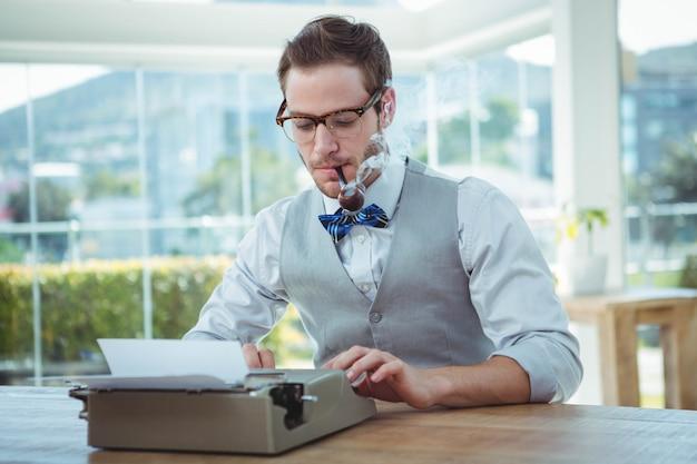 Homem bonito, usando a máquina de escrever à moda antiga no escritório brilhante