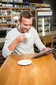 Homem bonito usando computador tablet e tomando um café