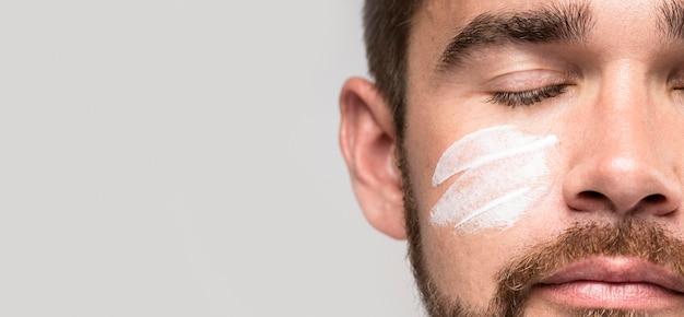 Homem bonito usando creme facial enquanto está de olhos fechados