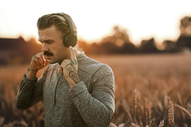 Homem bonito usando fones de ouvido sem fio e mídia remixada com vista da natureza