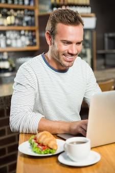 Homem bonito usando laptop e tendo um croissant