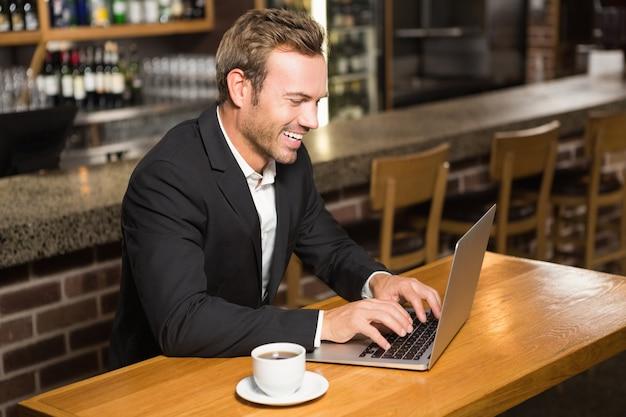 Homem bonito usando laptop e tomando um café