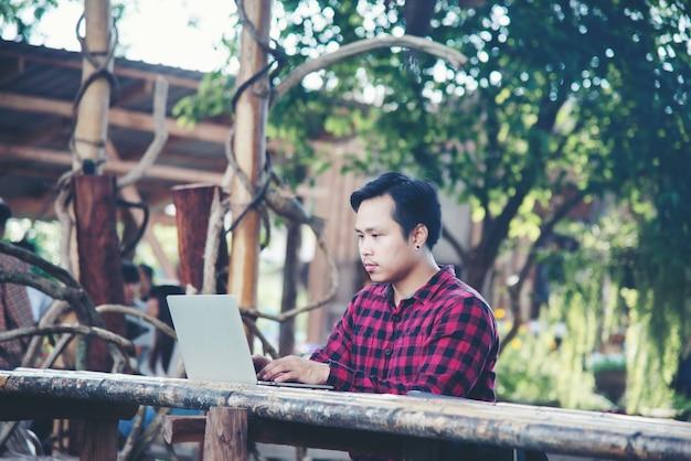 Homem bonito usando laptop na natureza viagens
