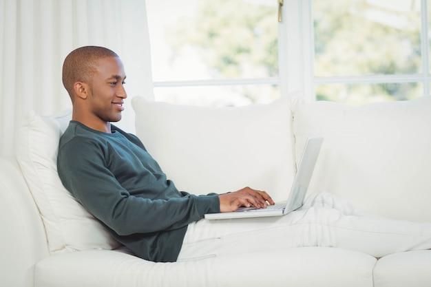 Homem bonito usando laptop no sofá