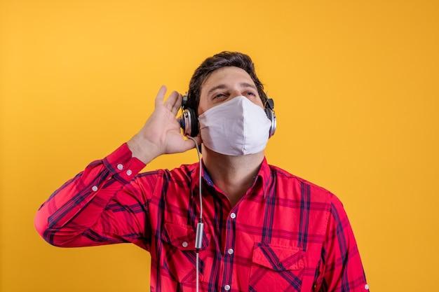 Homem bonito usando máscara cirúrgica para se proteger de cobiça e fones de ouvido