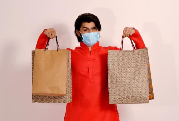 Homem bonito usando máscara e mostrando sacolas de compras, vista frontal, compras seguras