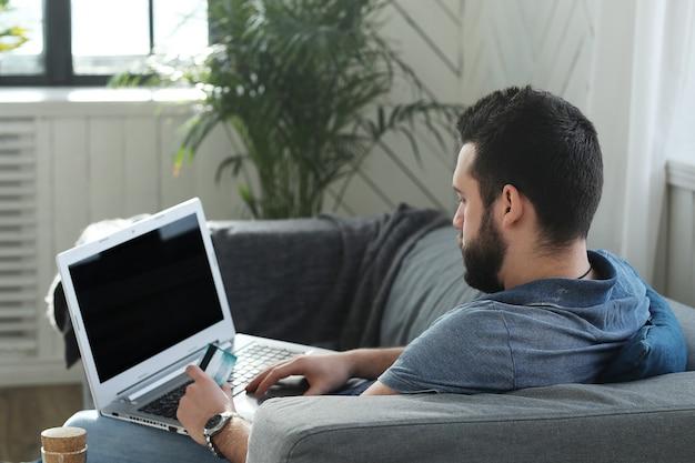 Homem bonito usando o laptop em casa. conceito de teletrabalho