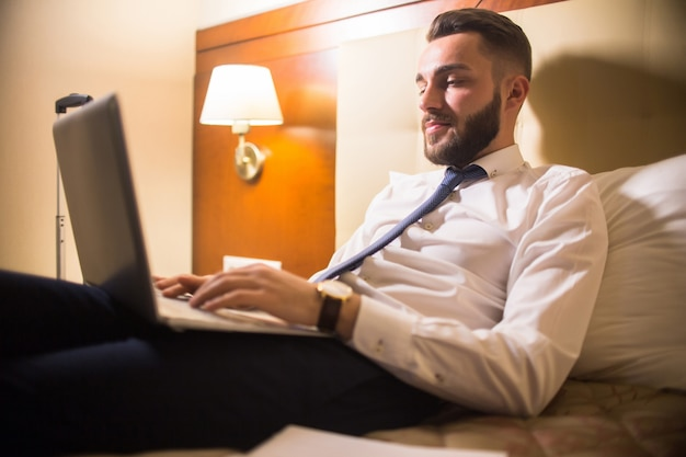 Homem bonito, usando o laptop na cama
