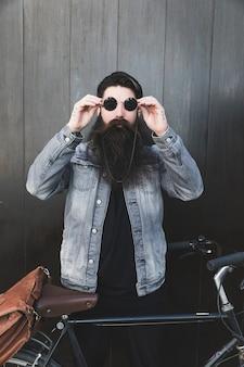 Homem bonito, usando óculos escuros em pé perto de bicicleta