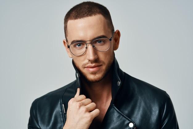 Homem bonito usando óculos, jaqueta de couro de cabelo curto, posando de moda