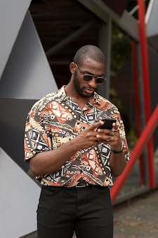 Homem bonito usando smartphone moderno ao ar livre