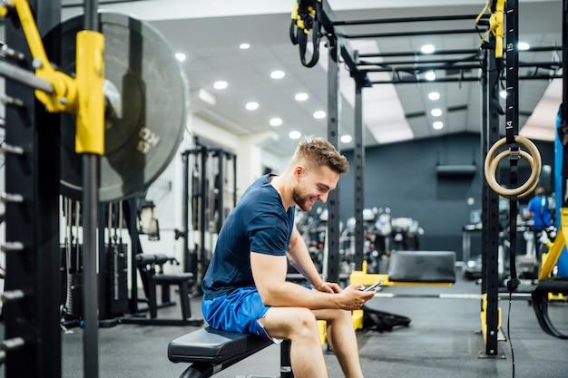 Homem bonito usando smartphone no ginásio