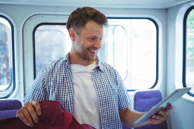 Homem bonito usando tablet digital no trem