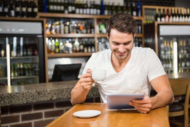 Homem bonito usando tablet e tomando café