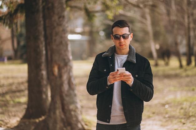 Homem bonito, usando telefone no parque