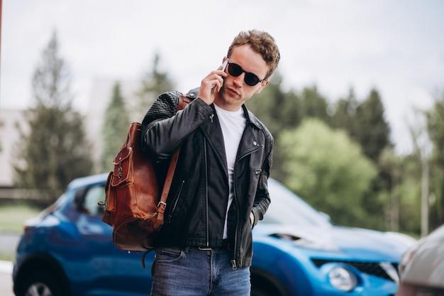 Homem bonito, usando telefone pelo carro