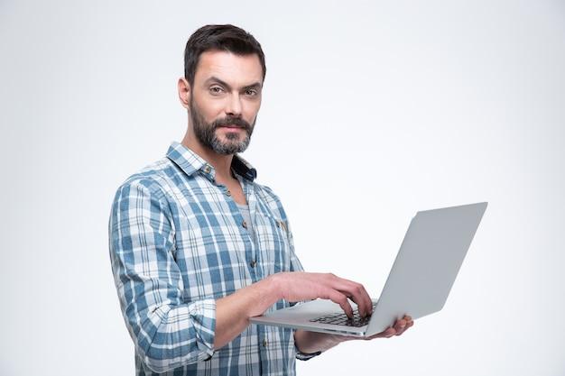 Homem bonito usando um laptop e parecendo isolado em uma parede branca