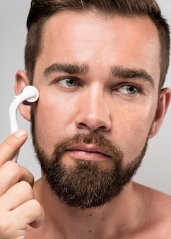 Homem bonito usando um rolo para limpar o rosto