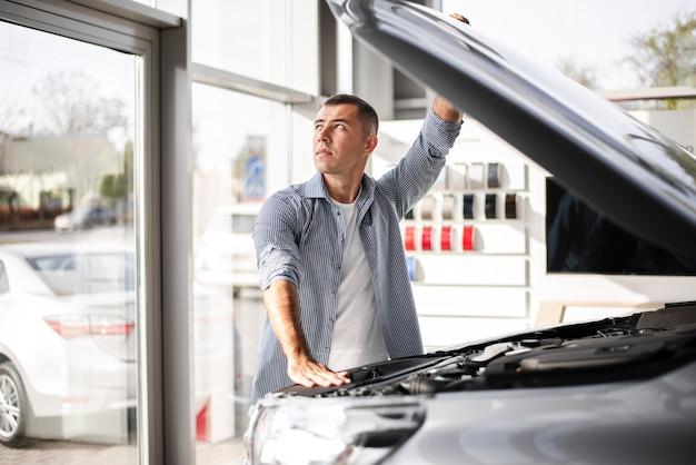 Homem bonito, verificando um carro na concessionária