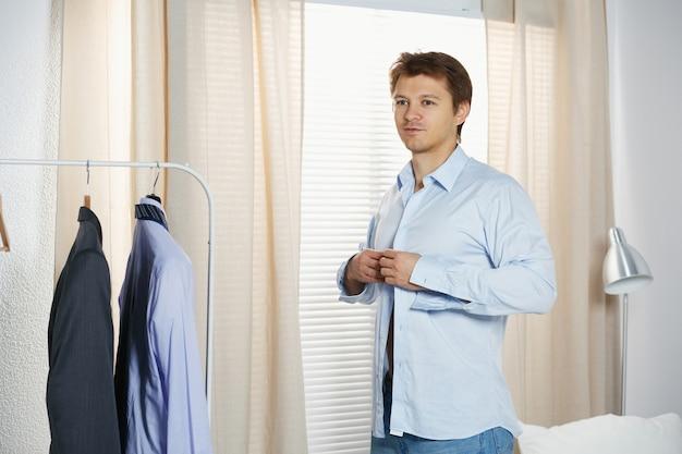 Homem bonito, vestindo a camisa em pé perto da janela em seu quarto de manhã. preparando-se para algum evento ou novo dia de trabalho.