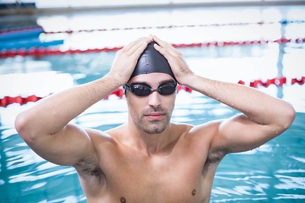 Homem bonito vestindo boné de natação e óculos de proteção na piscina