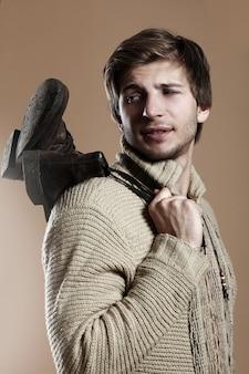 Homem bonito, vestindo botas e roupas de inverno