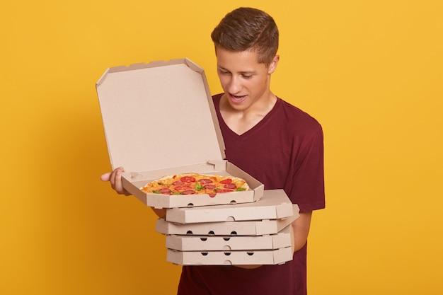 Homem bonito, vestindo camiseta casual da borgonha, segurando a pilha de caixas de pizza nas mãos