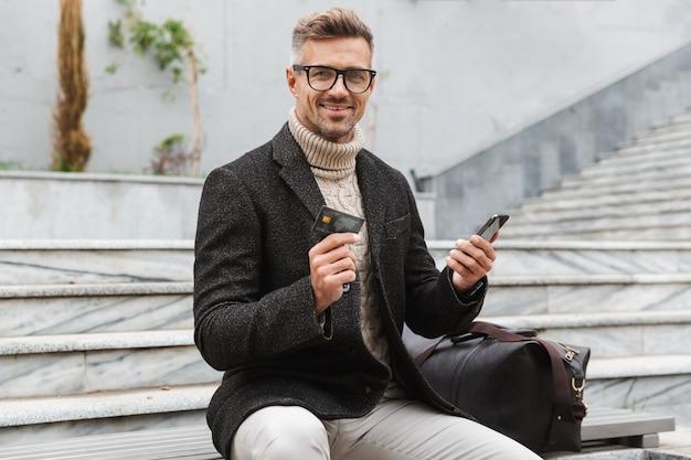 Homem bonito vestindo jaqueta fazendo compras online com o celular e cartão de crédito enquanto está sentado ao ar livre
