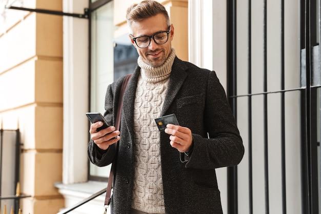 Homem bonito vestindo um casaco, caminhando ao ar livre, fazendo compras online com o celular e o cartão de crédito