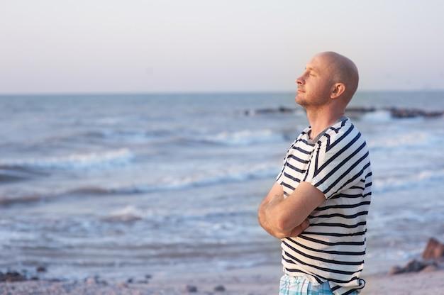 Homem bonito, vestindo uma camiseta listrada, respirando em frente ao oceano na praia.