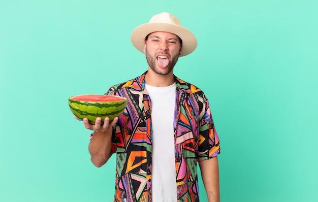Homem bonito viajante com atitude alegre e rebelde, brincando e mostrando a língua e segurando uma melancia. conceito de férias