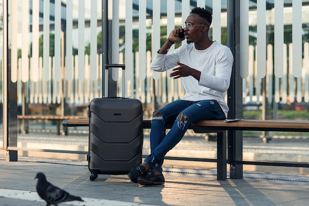 Homem bonito viajante com uma mala sentado no ponto de ônibus