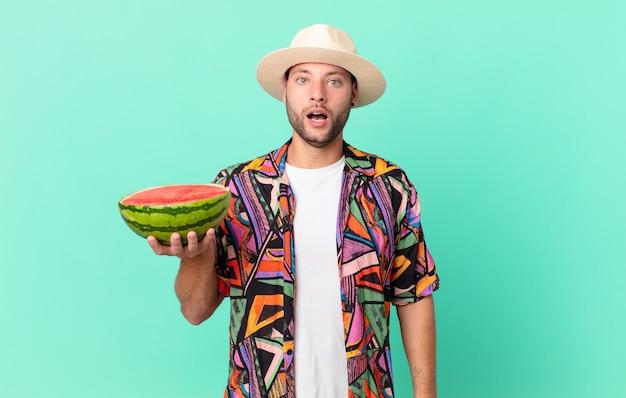 Homem bonito viajante parecendo muito chocado ou surpreso e segurando uma melancia. conceito de férias