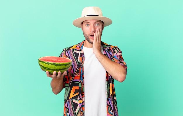 Homem bonito viajante se sentindo chocado e com medo e segurando uma melancia. conceito de férias
