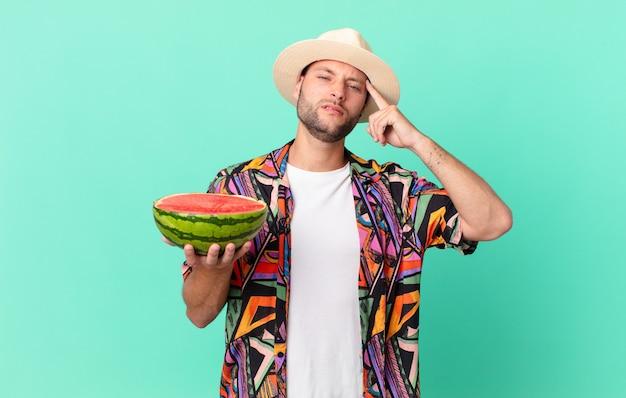 Homem bonito viajante se sentindo confuso e perplexo, mostrando que você está louco e segurando uma melancia. conceito de férias