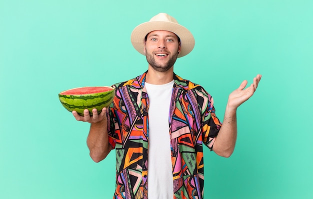 Homem bonito viajante se sentindo feliz e surpreso com algo inacreditável e segurando uma melancia. conceito de férias