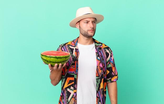 Homem bonito viajante se sentindo triste, chateado ou com raiva e olhando para o lado e segurando uma melancia. conceito de férias