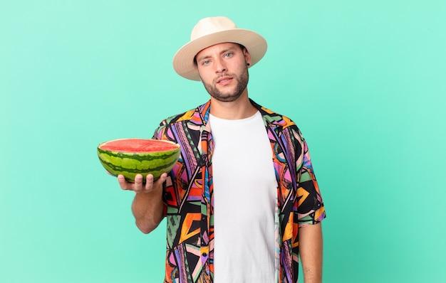 Homem bonito viajante sentindo-se perplexo e confuso e segurando uma melancia. conceito de férias