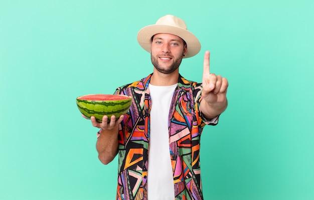 Homem bonito viajante sorrindo com orgulho e confiança, fazendo o número um e segurando uma melancia. conceito de férias