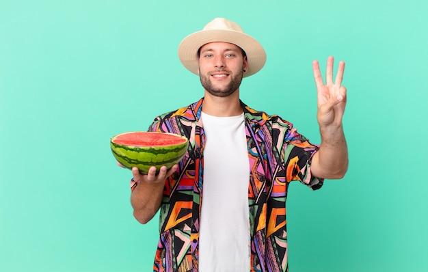 Homem bonito viajante sorrindo e parecendo amigável, mostrando o número três e segurando uma melancia. conceito de férias