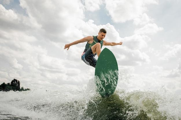 Homem bonito wakesurf no quadro rio abaixo contra o céu nublado e árvores