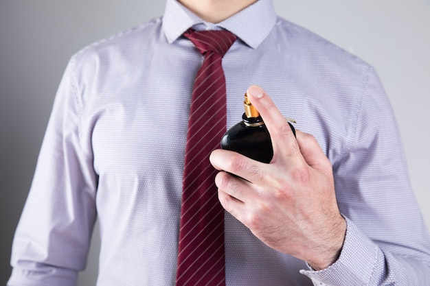 Homem borrifa perfume na parede cinza.