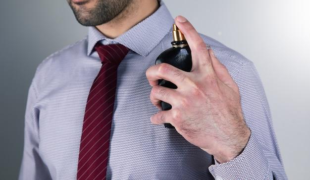 Homem borrifa perfume na superfície cinza.