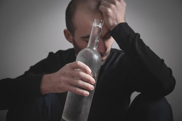 Homem branco alcoólatra com vodka.