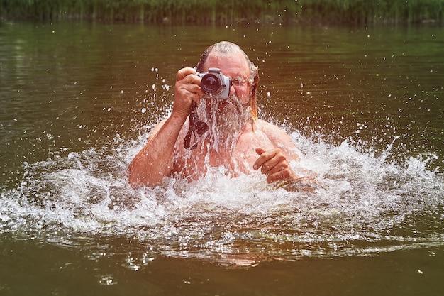 Homem branco barbudo maduro está nadando no rio e tirando fotos com uma câmera à prova d'água.
