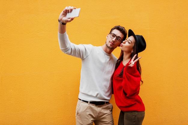 Homem branco bonito com barba e bonita mulher morena brincalhão fazendo auto-retrato e mostra sinais à mão.
